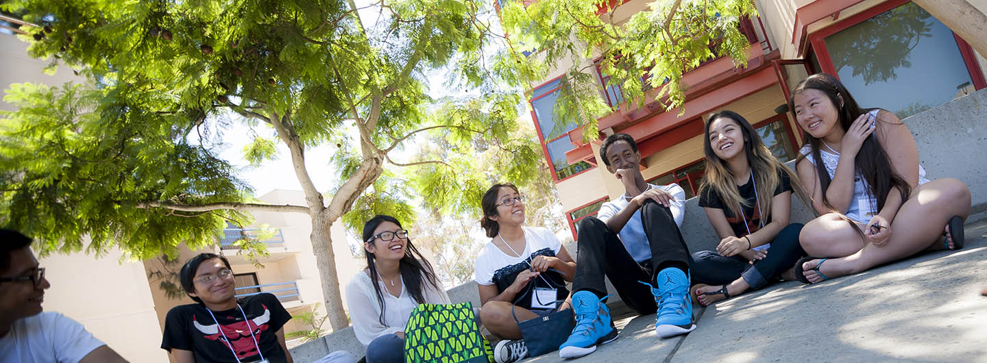 Photo of a small group of UC San Diego students sitting on campus and talking with each other - Center for Student Involvement - Communication and Leadership