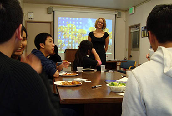 Student leadership workshop at UC San Diego - students sit around a table eating pizza in foreground while a standing facilitator talks with the group