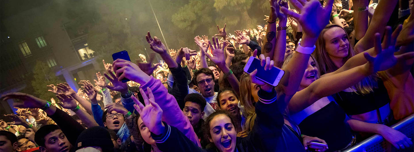 UC San Diego students cheer in front of a nighttime concert stage