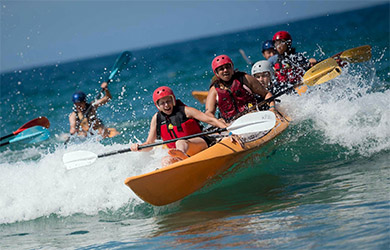 UC San Diego - Welcome Week event - Meet the Beach 2018 - students in kayak surfing a wave at La Jolla Shores beach