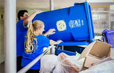 UC San Diego students participate in a day of service - two students empty a large trash bin
